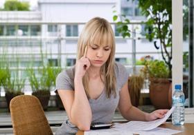 Junge Frau kontrolliert zu Hause Rechnungen
