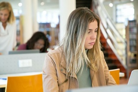 Junge Frau lernt an Laptop