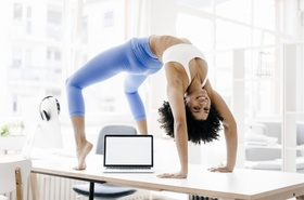 junge Frau macht Yoga auf ihrem Schreibtisch