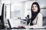 junge Frau mit Kopftuch arbeitet an Desktop