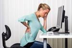 Junge Frau mit Rückenproblemen am Arbeitsplatz