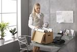 Junge Frau räumt in Büro Umzugskarton ein