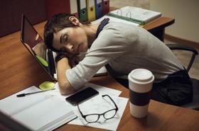 junge Frau schläft erschöpft auf ihrem Laptop ein