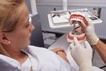 Junge Frau sitzt auf Behandlungsstuhl beim Zahnarzt