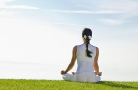 junge Frau sitzt in Yoga Sitz auf Wiese