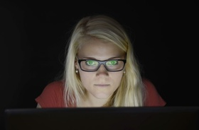 junge Frau starrt im Dunkeln vor Laptop