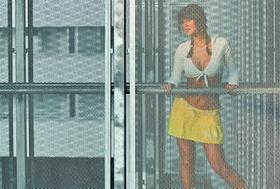 Junge Frau steht in Minirock und Top auf Galerie