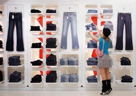 Junge Frau steht vor Regal einer Boutique