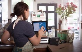 Junge Frau tippt etwas in elektronische Kasse ein