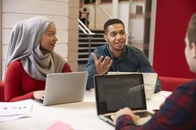 junge internationale Menschen diskutieren an Schreibtisch vor Laptops