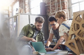 Designers working at laptop in workshop
