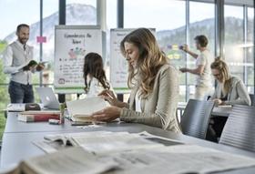 junge Mitarbeiterin blättert während Seminars in Unterlagen