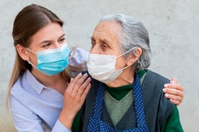 Portrait of friendly caregiver posing with elderly ill woman wearing surgical mask because of covid-