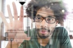 junger afrikanisch aussehender Mann bedient transparentes Touchscreen