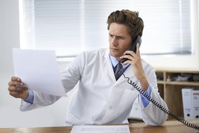 Shot of a concerned doctor sitting in his office and talking on the phone while looking over paperwo