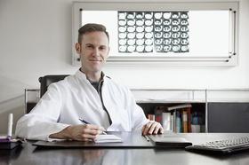 Junger Arzt sitzt am Schreibtisch und schaut in die Kamera