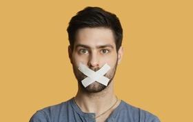 Junger Erwachsener mit Tape beklebtem Mund