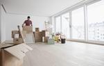 Junger Mann in Wohnung mit Kartons Leiter Möbel