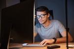 Junger Mann mit Brille sitzt vor Computer und schaut angestrengt auf Bildschirm