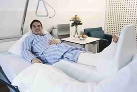Junger Mann mit gebrochenem Bein im Krankenbett
