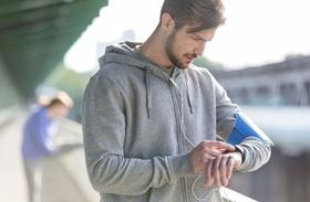 junger Mann schaut beim Sport auf Uhr