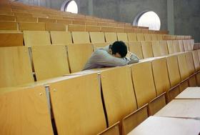Junger Mann schläft gelangweilt in Hörsaal
