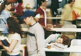 Junger Mann schläft in Hörsaal, junge Leute gehen hin und her