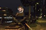 junger Mann sitzt auf Parkbank und hört Musik im Dunkeln