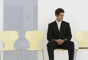 junger Mann sitzt, neben ihm leere Stühle