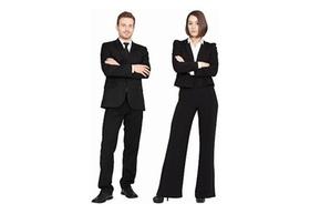 Junger Mann und junge Frau in Anzug schauen selbstsicher bis arrogant