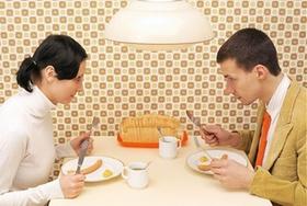 Junger Mann und junge Frau sitzen am Tisch und essen