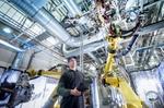 junger Mitarbeiter in Fabrik arbeitet mit Roboter