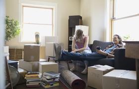 Junges Paar auf Couch sitzend und umgeben von Umzugskartons