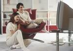 Junges Paar, sitzen auf und neben modernem Sessel vor Fernseher