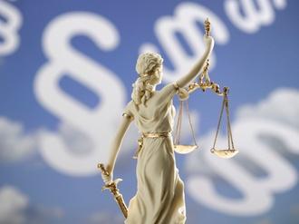 Justitia-Figur vor Paragraphenzeichen