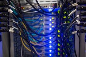 Kabelgewirr von Server mit blauen Lichtern im Hintergrund