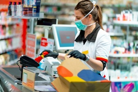 Woman cashier wearing protective face mask and gloves to prevent viruses, scanning disinfection prod