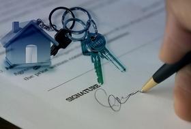 Kaufvertrag mit Hausmodell und Wohnungschlüssel