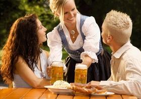 Kellnerin und zwei Gäste im Biergarten