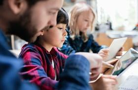 Kind liest mit Betreuung/Lehrer auf Tablet