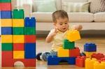 Kind spielt mit bunten Plastiksteinen
