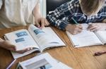 Kinder arbeiten zusammen an Arbeitsbuch