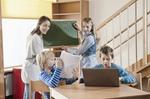 Kinder lernen an Tafel und Computer