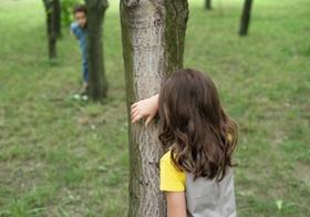 Kinder spielen hinter Baeumen verstecken