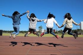 Kinder spielen im Wohnviertel 4 Mädchen springen in die Luft