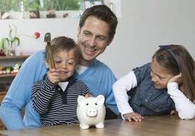 Kinder und Vater zerschlagen Sparschwein