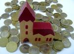 Kirche als Bauklotz auf Münzen