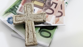 Bundle of euro notes with cross on white background