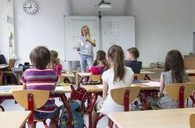 Klassenraum mit Lehrer und Kindern in der Grundschule