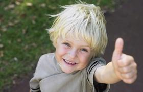 Kleiner Junge zeigt fröhlich Daumen hoch